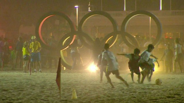 Children playing football in front of Olympic rings