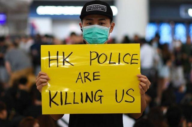 """香港国际机场一号客运大楼内一名示威者举着""""香港警察在杀害我们""""标语牌(12/8/2019)"""