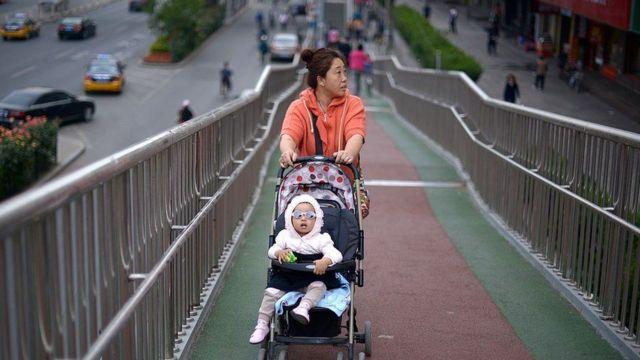 চীনে এক নারী শিশুকে নিয়ে রাস্তায় হাঁটছেন