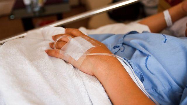 Paciente em cama de hospital - foto focaliza a mão