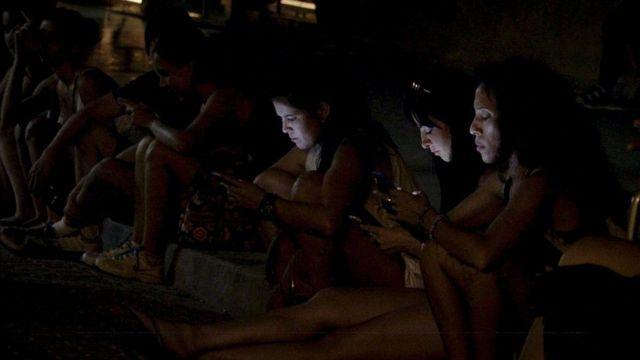 Jovens sentados na praça para acessar a internet