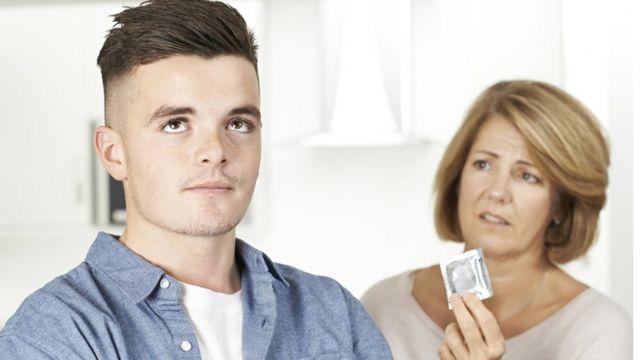 Mãe mostra uma camisinha para o filho adolescente, que revira os olhos