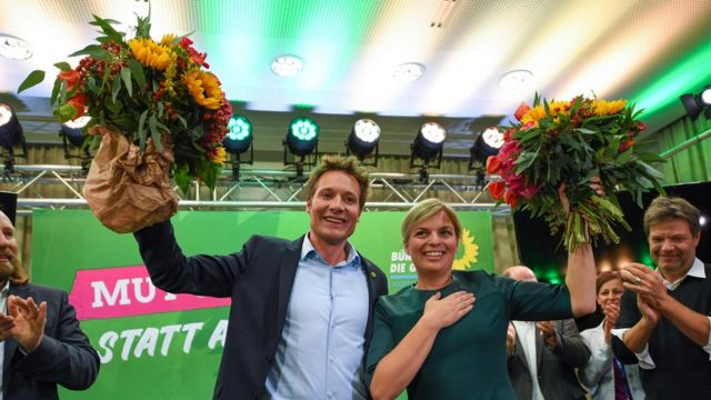 Green leaders Ludwig Hartmann and Katharina Schulze celebrate after hearing exit polls