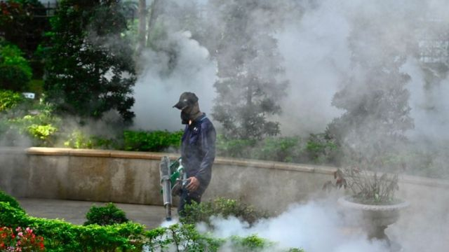 A mask-clad worker disinfects an area to prevent the spread of Covid-19 in Xindian district in New Taipei City, Taiwan