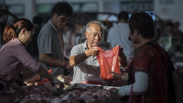 A butcher sells pork at a market in China