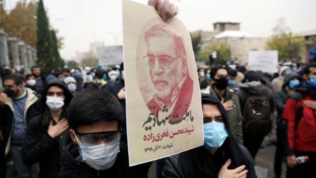 شاب إيراني يحمل صورة فخري زادة في مظاهرة في طهران تنديدا باغتياله.