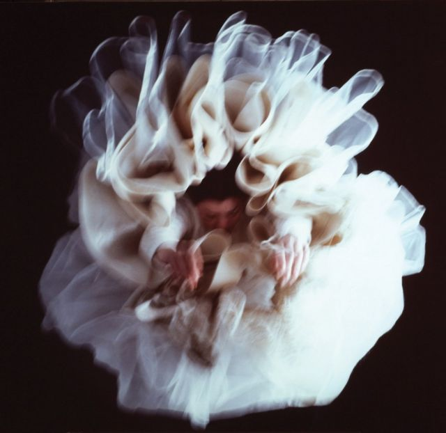 A blurred woman in a frilled dress