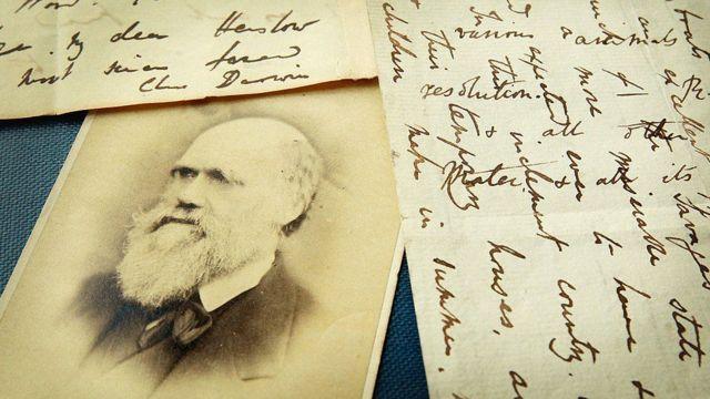 Una foto de Darwin con unas cartas
