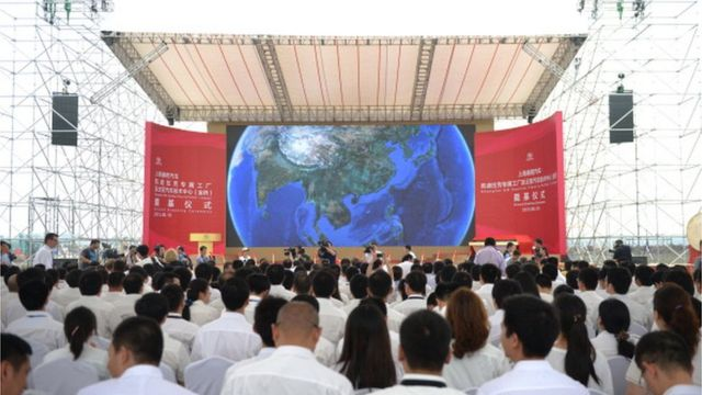 Visitors wait for the start of the ceremony on a $1.3bn General Motors plant in Shanghai on June 19, 2013.