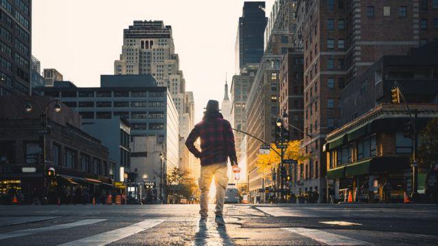 Un hombre de espaldas parado en una calle vacía de Nueva York.