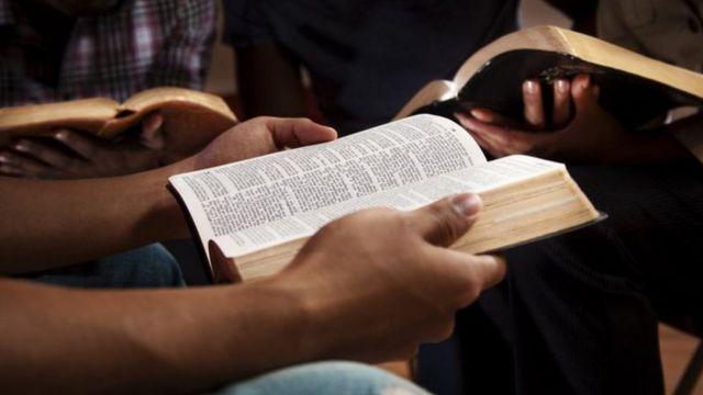 Uma pessoa segurando uma Bíblia aberta
