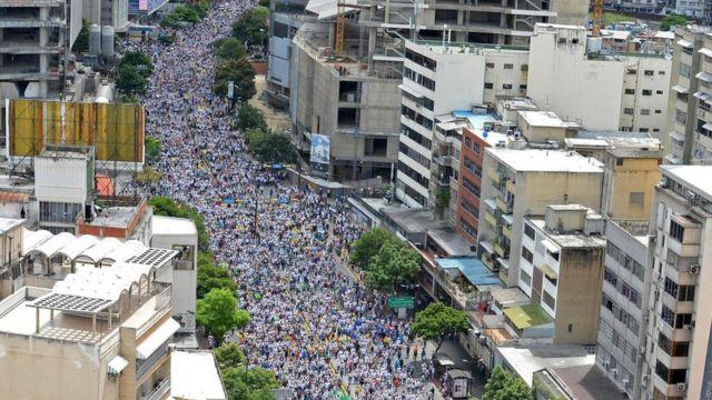 Una multitud camina por una gran avenida en Caracas.