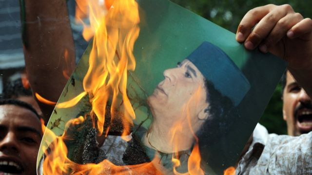Libyan protesters burn an image of the country's leader Muammar Gaddafi in 2011