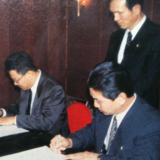 Park Ki-young assinando um contrato com a AJA Communications, da Coreia do Norte