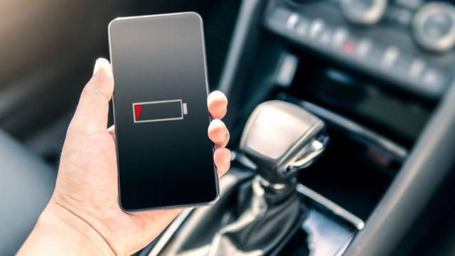 Persona sosteniendo un teléfono sin batería.