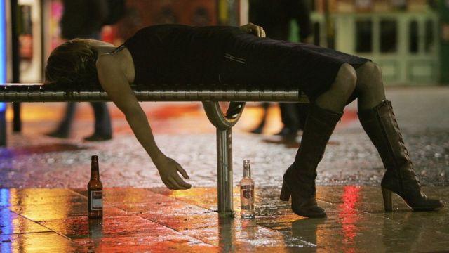 Mujer borracha en una silla en la calle