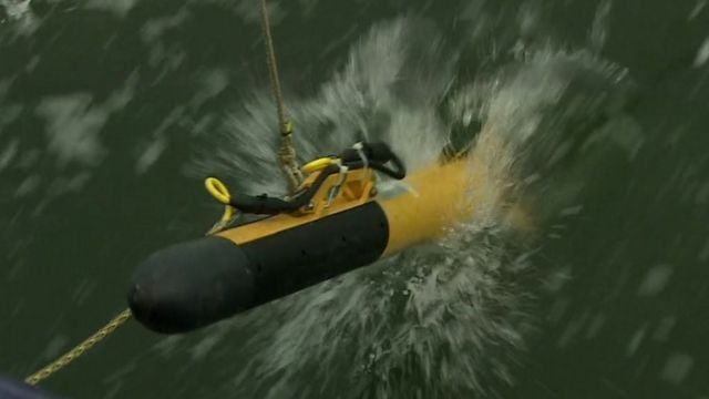 A towfish, or deep-water detector, being launched