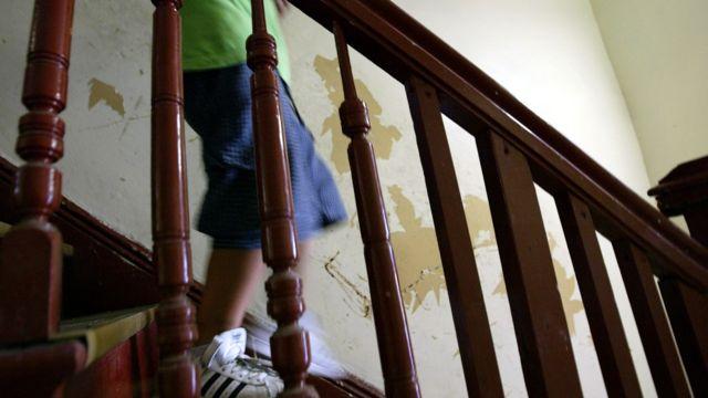 Niño bajando una escalera en una casa con paredes con pintura descascarada