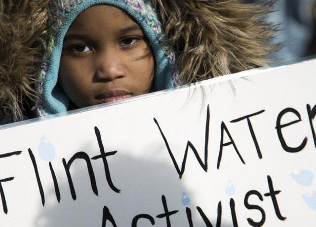 Niño protestando en Flint.