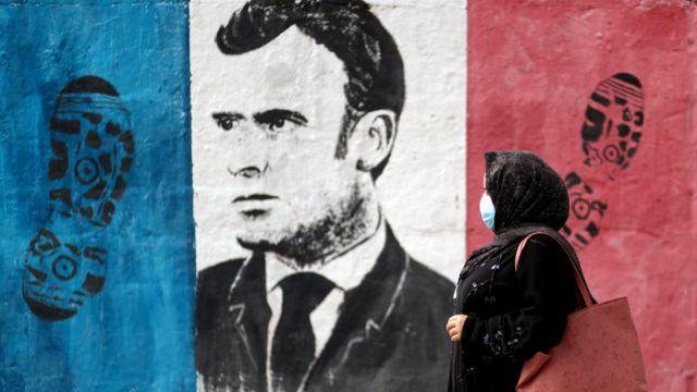 Gazze'de Fransa bayrağı üstünde ayak izi ve Macron'un yüzünün olduğu bir duvar resmi.