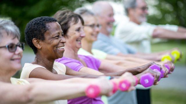 Seis idosos enfileirados olhando para frente, sorrindo e segurando halteres