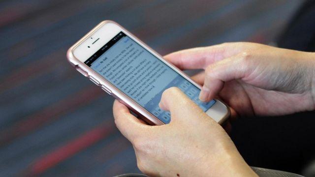 Mulher lê e-mail no celular