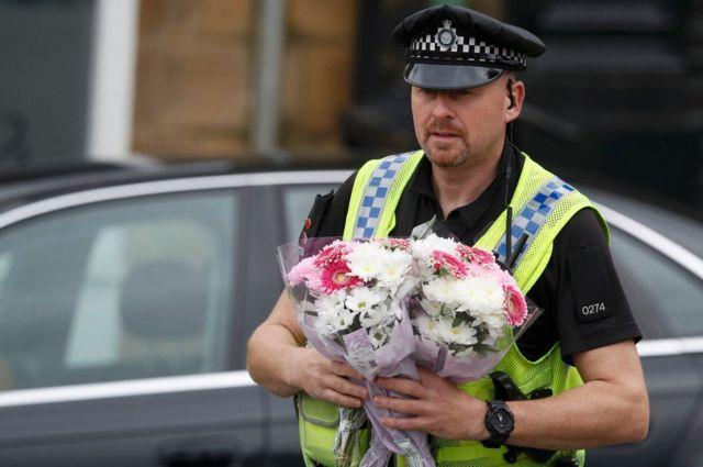 捜査現場の外に置かれた花束を中に運ぶ警官