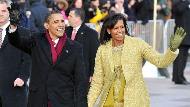 Barack e Michelle Obama acenando para o público