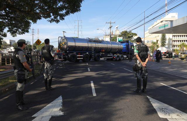 Policiais nas proximidades de posto de combustível