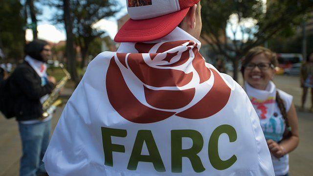 Un simpatizante de la FARC envuelto en la bandera con el logo del nuevo partido en el cierre de su congreso en Bogotá.