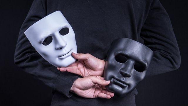Un hombre sujeta una máscara blanca y otra negra.
