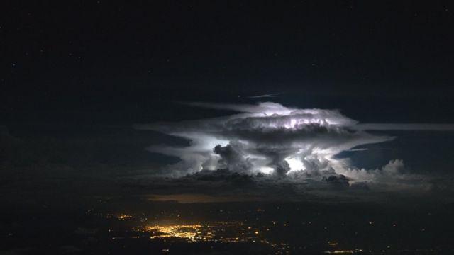 Nubes blancas en un cielo oscuro sobre las luces de una ciudad