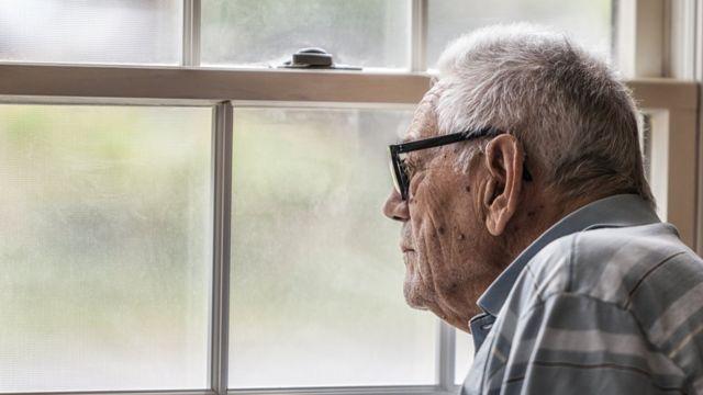 Anciano mirando a través de una ventana.