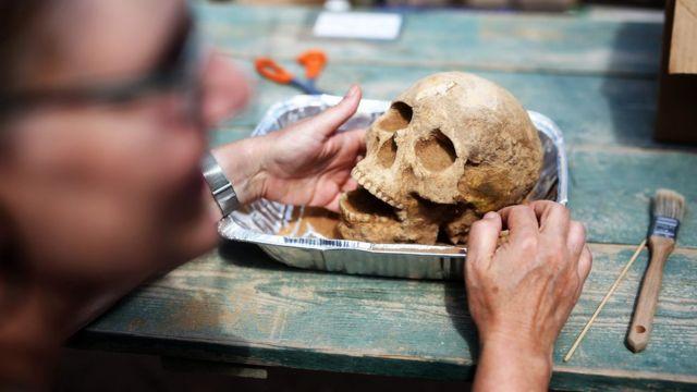 La antropóloga y patóloga Sherry Fox muestra un cráneo descubierto en el sitio de la excavación del primer descubrimiento de un cementerio filisteo, el 28 de junio de 2016.