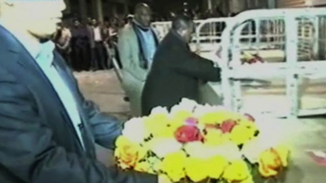 Flowers being laid on top of coffins.