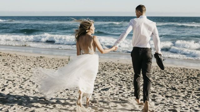 A married couple walking on the beach