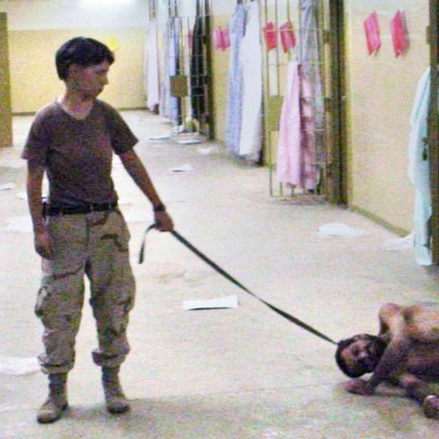Militar estadounidense Lynndie England sosteniendo a un prisionero de un bozal por el cuello