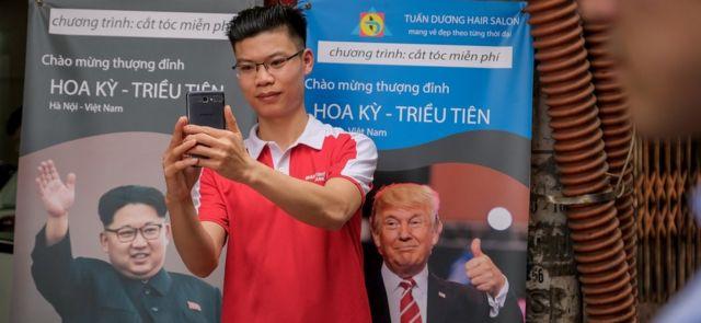 Hanoi'deki zirve afişi önünde selfi çeken biri