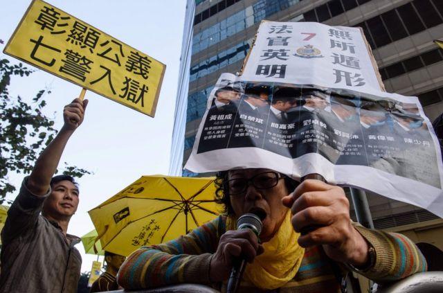 """曾健超的支持者也在法庭外手举""""彰显公义,七警入狱""""的标语牌示威。"""