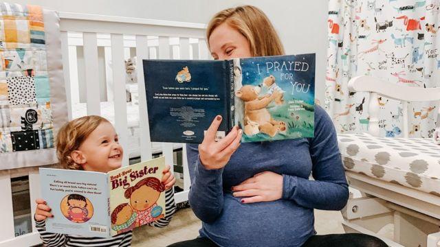 Тина Гибсон читает книгу своей дочери Эмме