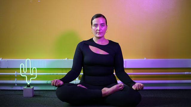 Nicki Briant, de cabelo preso e roupas de ginástica, sentada com as pernas cruzadas e as mãos em postura de ioga