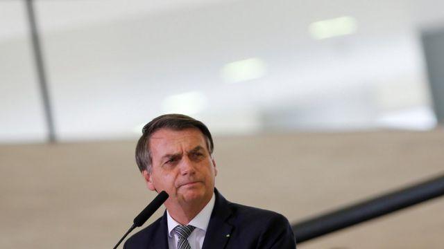 Bolsonaro olha para o lado em frente a microfone
