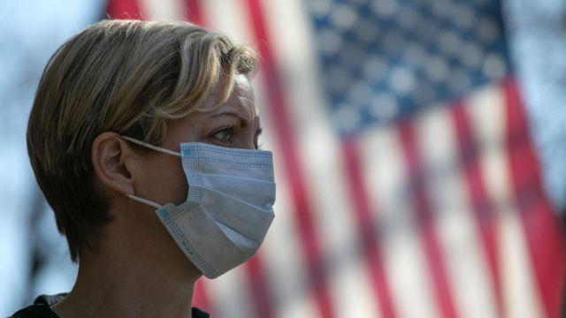 Una mujer usando una mascarilla junto a la bandera de Estados Unidos.