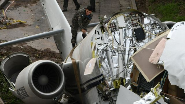 A military person climbs on top of the tail end of the collapsed plane