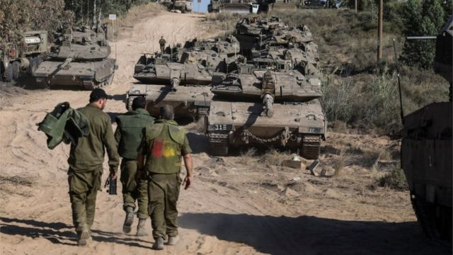 Israeli army walking near tanks