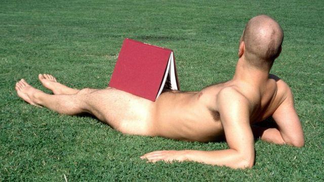 Homem nu com livro deitado na grama