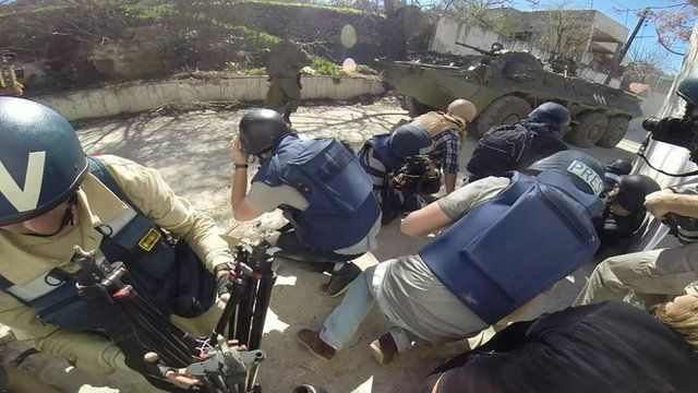 Journalists taking cover from explosions behind a tank in Latakia, Syria