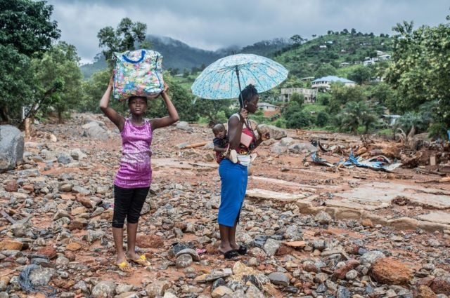 Women stand on the spot where their home once stood