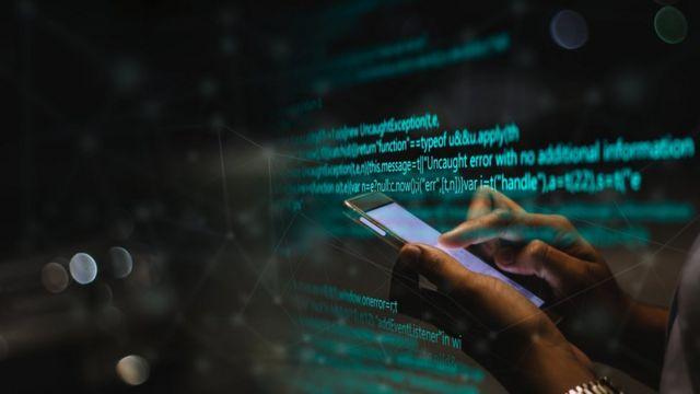 Pessoa mexendo em celular com códigos de computador sobrepostos