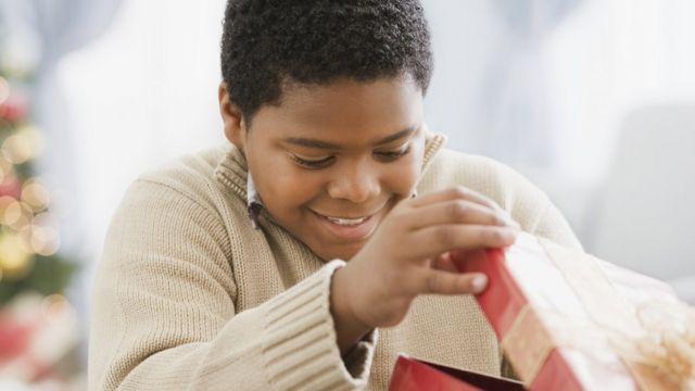Criança abrindo caixa de presente